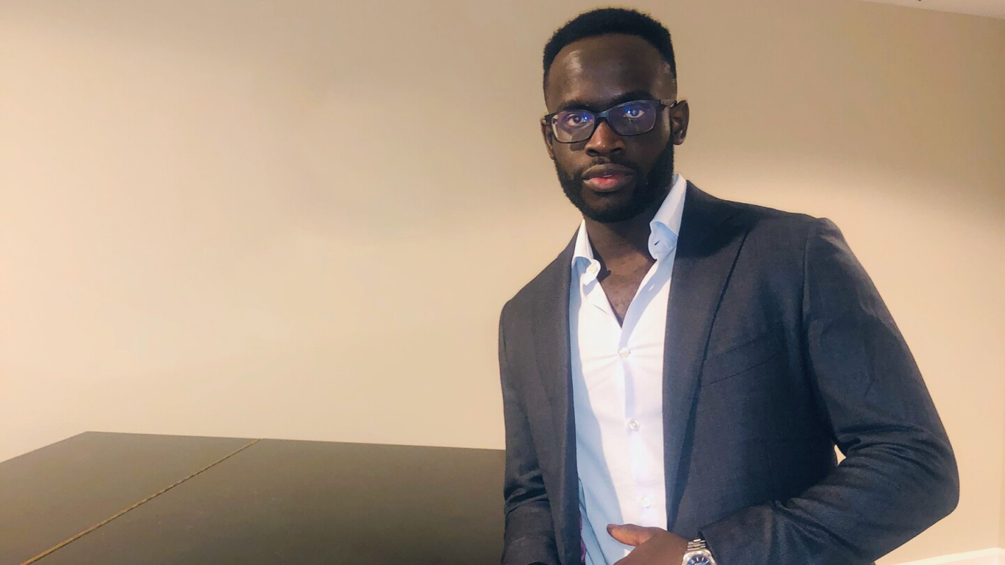 Oritseweyinmi Henry Ajagbawa poses in front of a wall in a suit jacket and a collared shirt, he is leaning on a shiny dark table