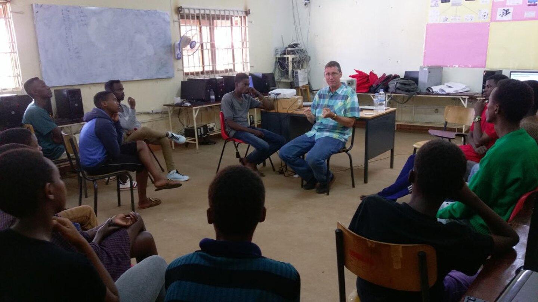 David Kosbie in a classroom with students in Rwanda