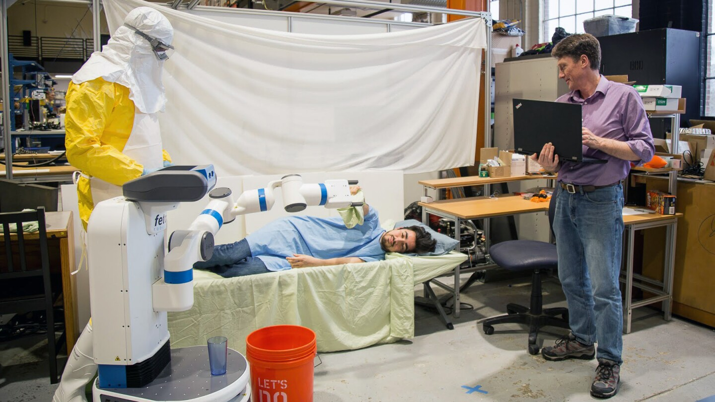 Bill Smart, far right, Oregon State University professor of robotics, and an Amazon Scholar, demonstrates an experiment simulating how robots might be used during Ebola outbreaks.