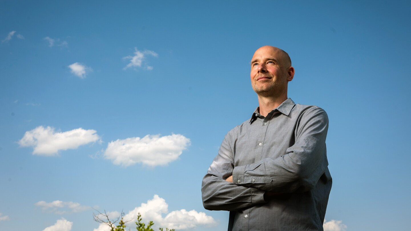 Philip Stier, the head of Atmospheric, Oceanic and Planetary Physics at the University of Oxford, is seen standing with his arms folded under a blue sky with some clouds in the background.