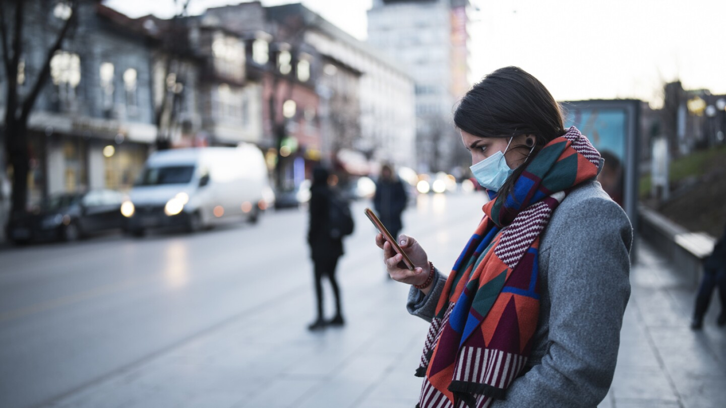 woman standing on sidewalk wearing face mask to protect against Covid 19