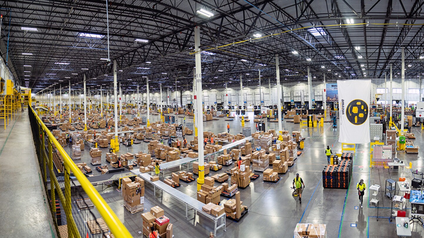 This picture is an overhead shot inside an Amazon center, workers can be seen moving amidst hundreds of boxes which sit on conveyor belts and carts, in the upper left foreground, a yellow railing extends into the distance.