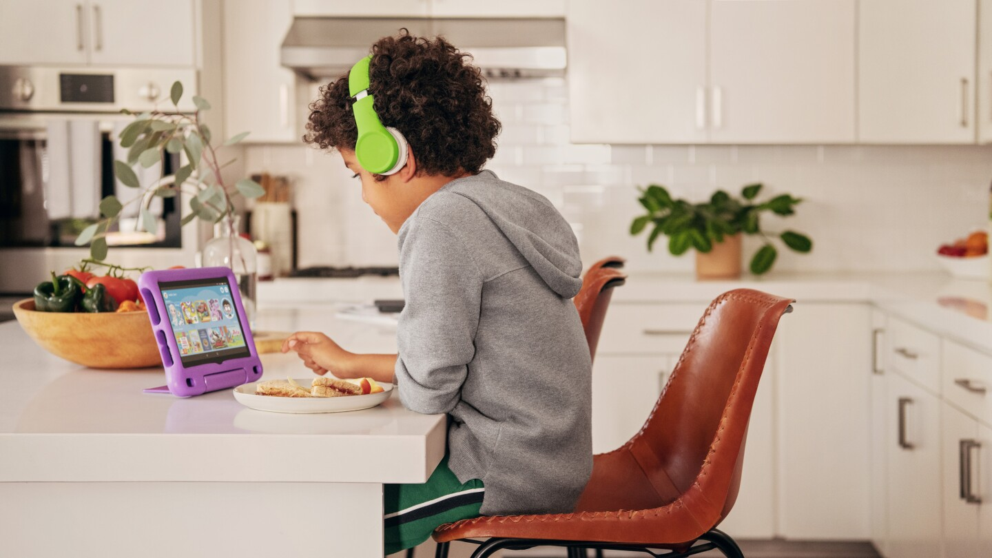 A child sits in a chair at a kitchen counter, wearing headphones while watching a Fire tablet